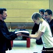 Seraina erhält, sichtlich erleichtert, ihre Urkunde und den mit dem Schülergrad-Abzeichen bestickten Anzug.